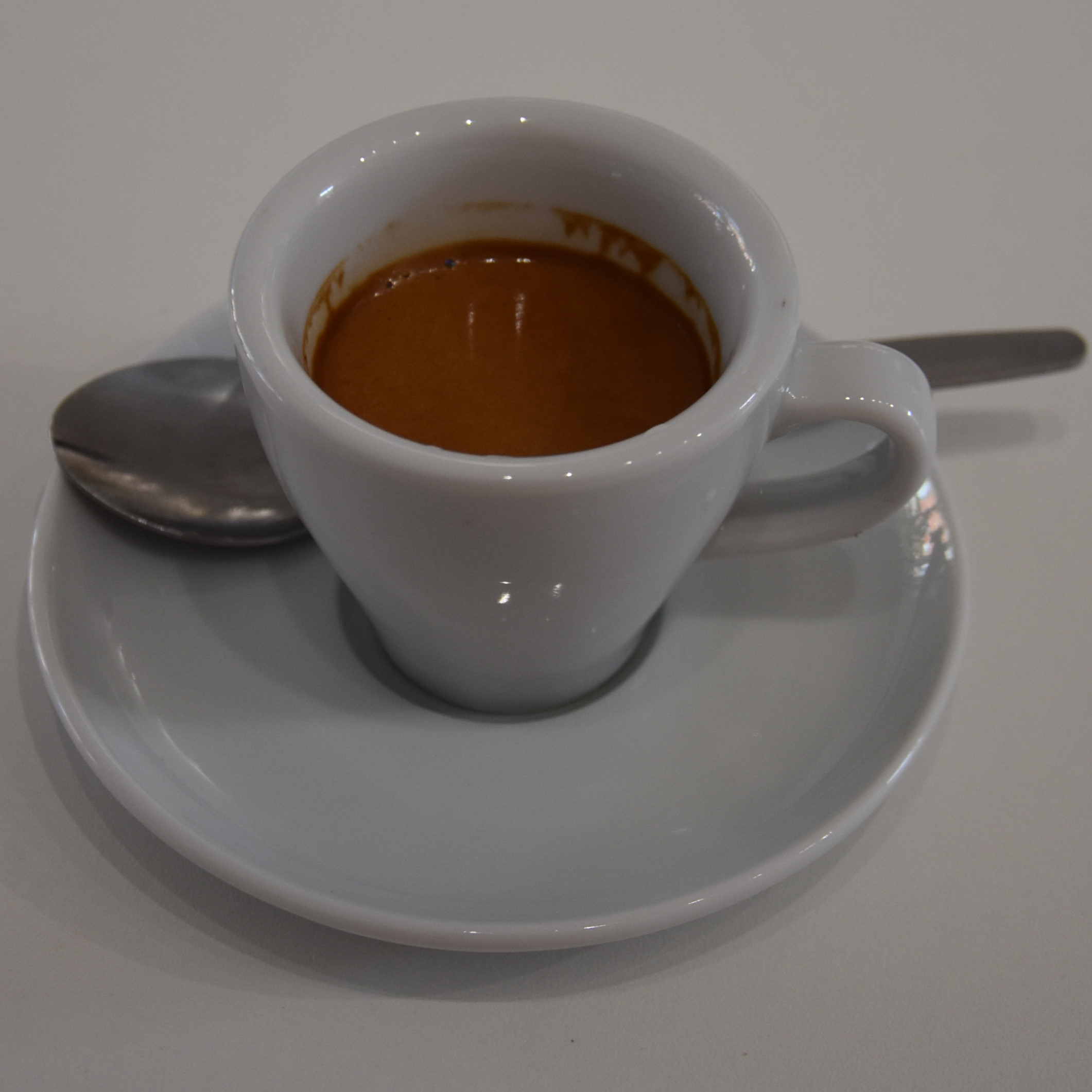 A shot of the Mayni coffee, served as an espresso in a classic white cup at Caffeina Coffi.