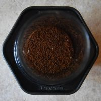 The view from above: an AeroPress, used in the conventional configuration, with 15 grams of ground coffee in the chamber, waiting for the hot water to be added.