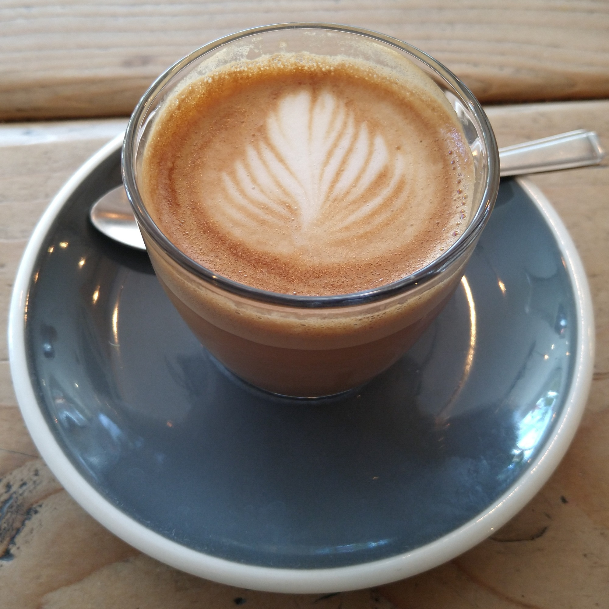 A cortado, served in a glass on a blue saucer, made with an exclusive coffee from Santa Ana in El Salvador and roasted by Nude Espresso for Bean and Hop.