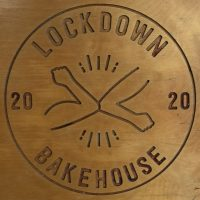 The Lockdown Bakehouse logo, carved into the top of one of the tables.