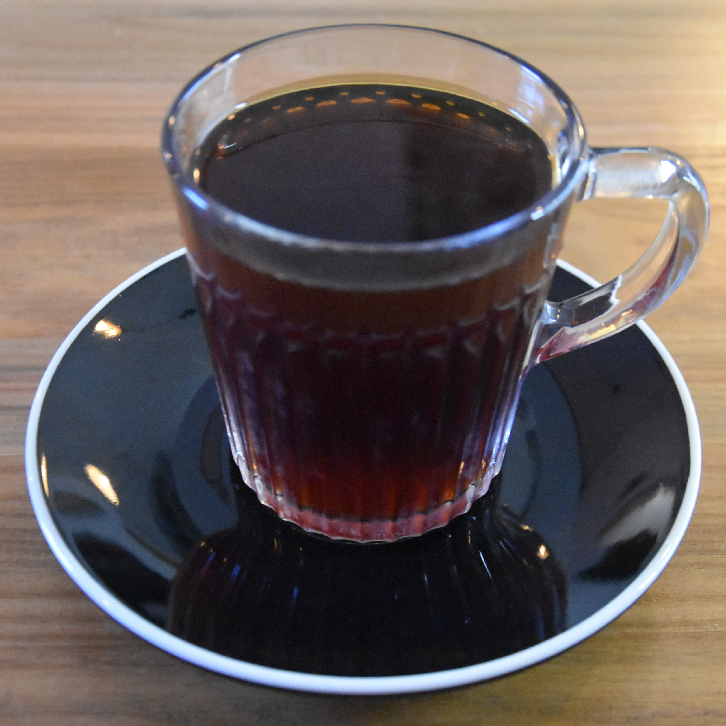 A V60 of the Worka Chelchelie, a natural yeast process coffee from Ethiopia, roasted by Yallah Coffee and served in a glass cup at MONIES in Putney.