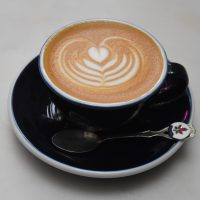 A classic flat white with some lovely latte art, served in a classic black cup at The Eclectic Collection.