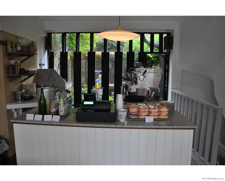 To business. The counter's at the back, kitchen to the left, espresso machine to the right.