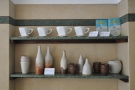 On the opposite side are two more retail shelves, with coffee kit and hand-made ceramics.