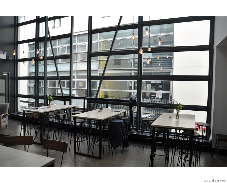 The space is dominated by the windows on the right, where there are these three tables.