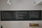 The menu is on the left-hand wall, to the left of the counter.
