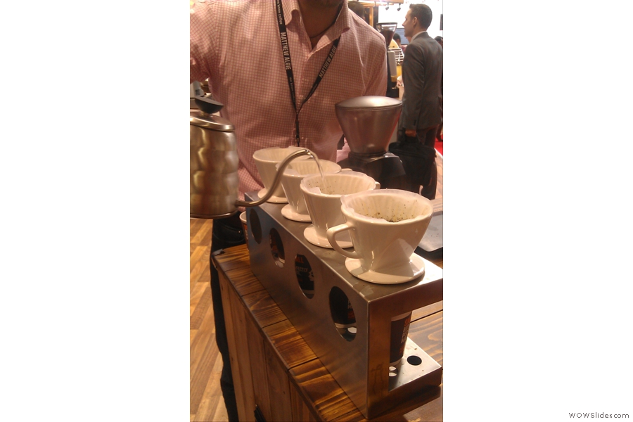 After wetting the filter papers, which washes out the paper taste and also serves to warm the cups, the coffee is added and a little water poured into each filter to allow the grounds to bloom.