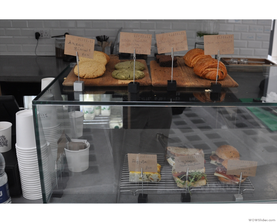 There is a limited selection of cake and sandwiches to the right of the counter.