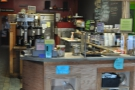 The main counter as seen from the door. It's what I would call 'busy'. The espresso machine is under what looks to be a cloud of steam...
