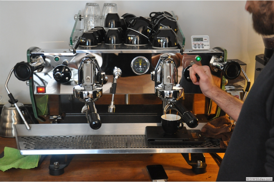 Baptiste at work. In case you think that the espresso machine has three spouts, the third stream at the back is a reflection in the extremely shiny espresso machine! Note the scales under the cup.