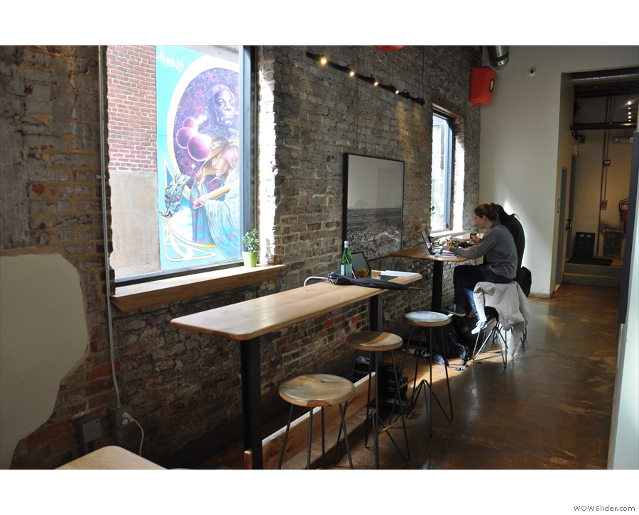 At the back, by the exposed brick walls, there are these bar-like tables.