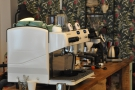 The whiite espresso machine has pride of place in the centre of the counter.
