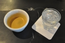 My resulting espresso, served in a handleless cup with a glass of water as standard.