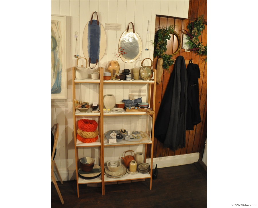 There are more shelves with things for sale against the right-hand wall. Plus coats. Not sure if the coats are for sale or if this is just a convenient coat-rack...