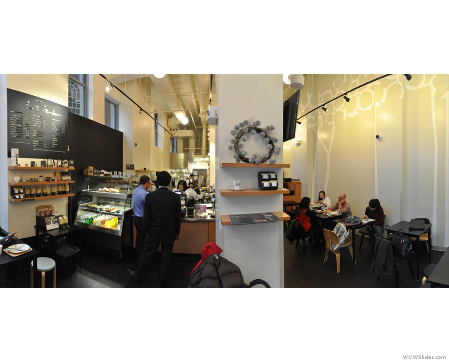 A panoramic view from just inside the door, looking towards counter (left) and seating (right).