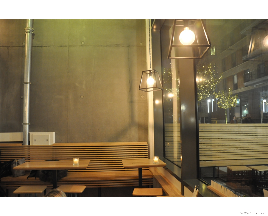 Against the far wall is a raised bench-seat with tables...