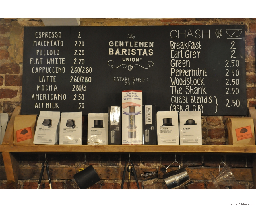 The menu is on the wall behind the counter, coffee on the left, tea on the right.