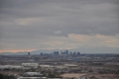 Downtown Phoenix with the sun setting behind the clouds/mountains to the west.