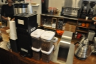 The various single-origins for the pour-over are in plastic bins on the counter top.