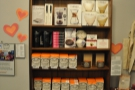 The retail shelves, with all sorts for sale, including merchandising, coffee kit...