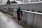 Japanese society's very personnel-intensive: a member of staff clears a train departure...