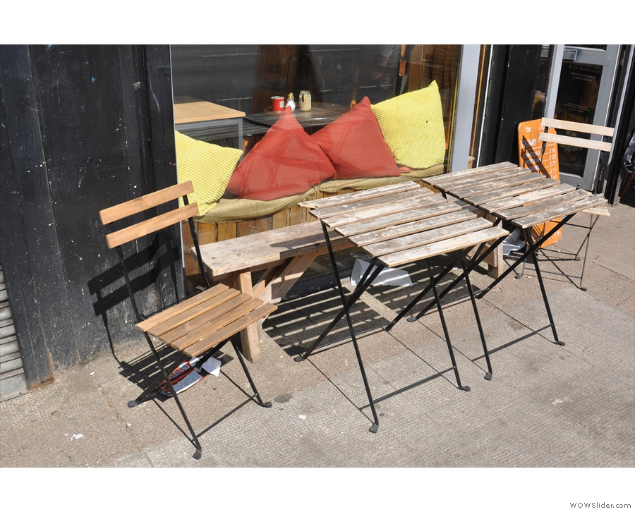 There's outside seating in the shape of this bench and its two tables on the busy street.