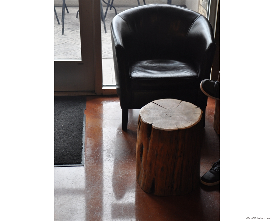 ... while to the left of the door, there's a pair of armchairs by a tree-trunk coffee table.