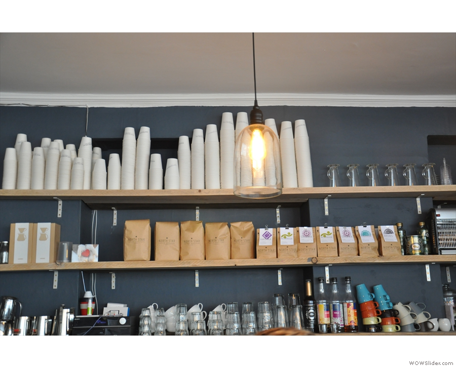 Bags and bags of coffee on the wall behind the espresso machine.