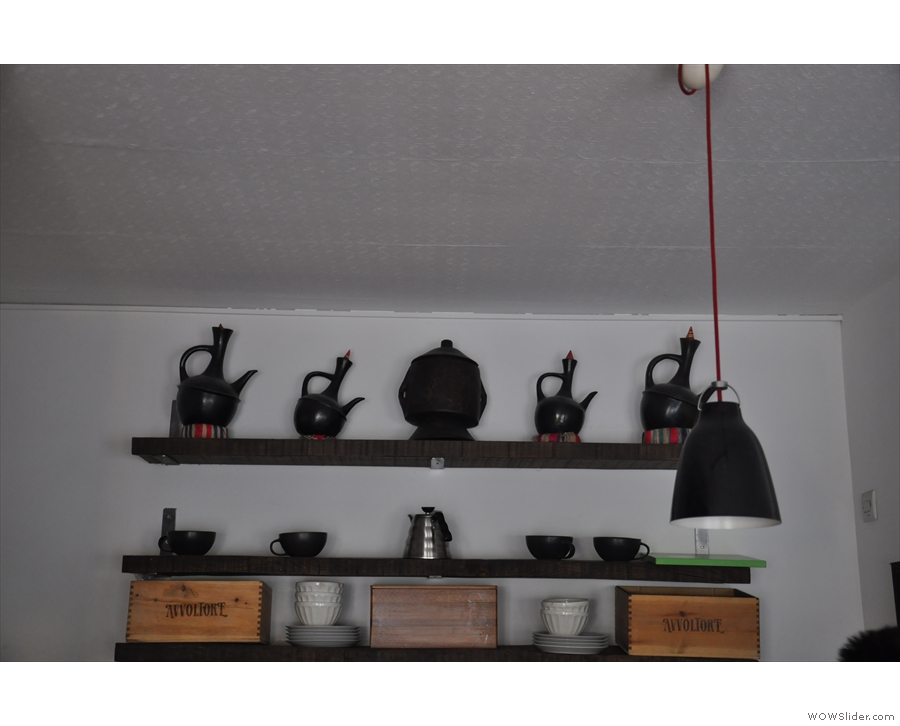 Meanwhile, on the wall at the back of the counter, are some traditional coffee pots.