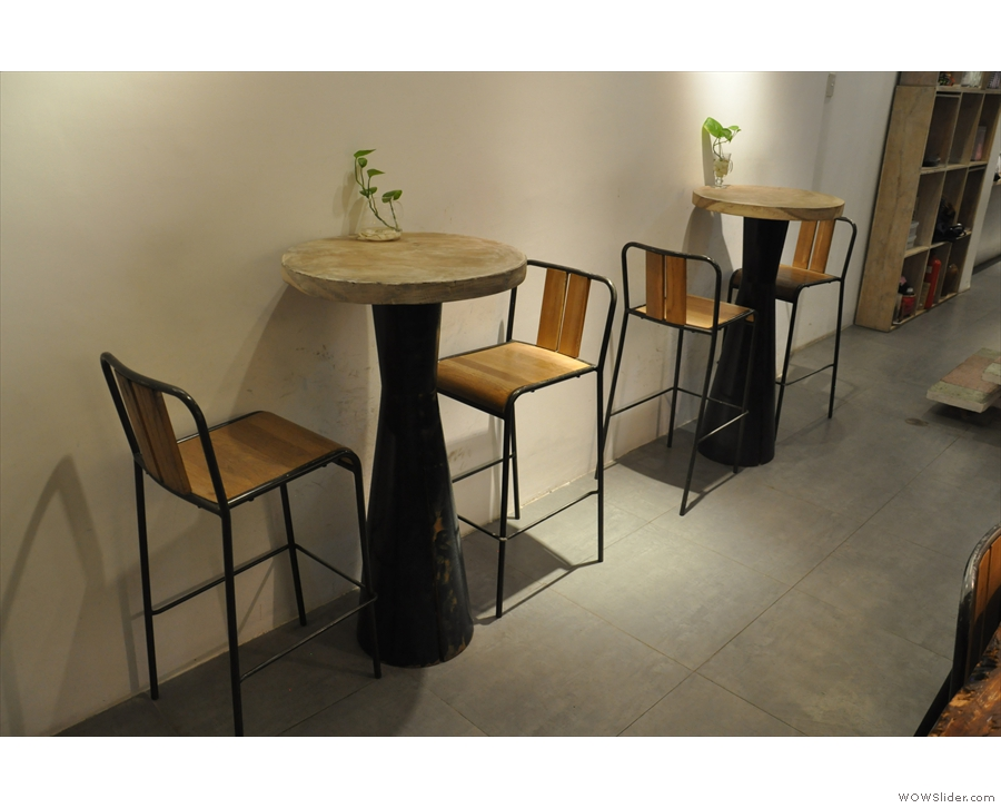 ... while opposite it are a pair of tables against the wall.