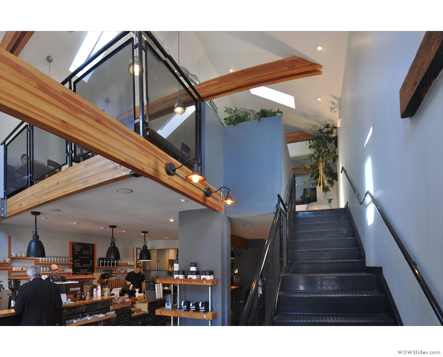 The stairs lead to an upstairs area at the back, extending into a mezzanine at the front.