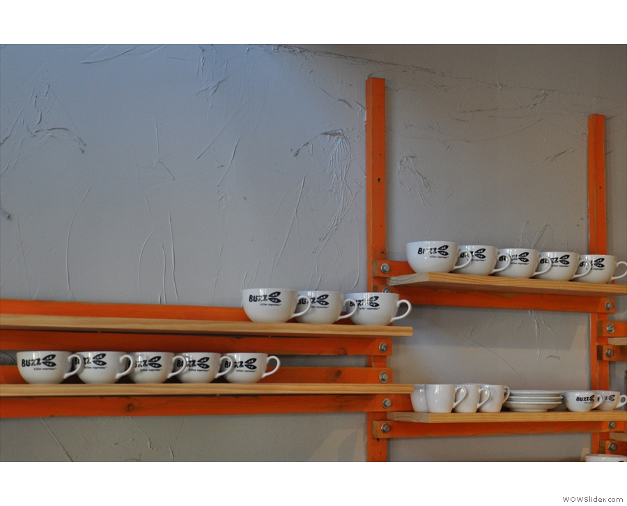 The cups line up on the wall behind the counter, waiting their turn to be used.