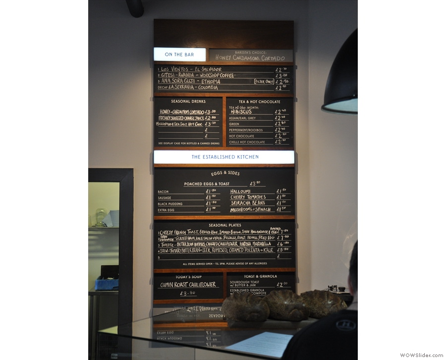 The menu is on the wall behind and to the left of the counter.