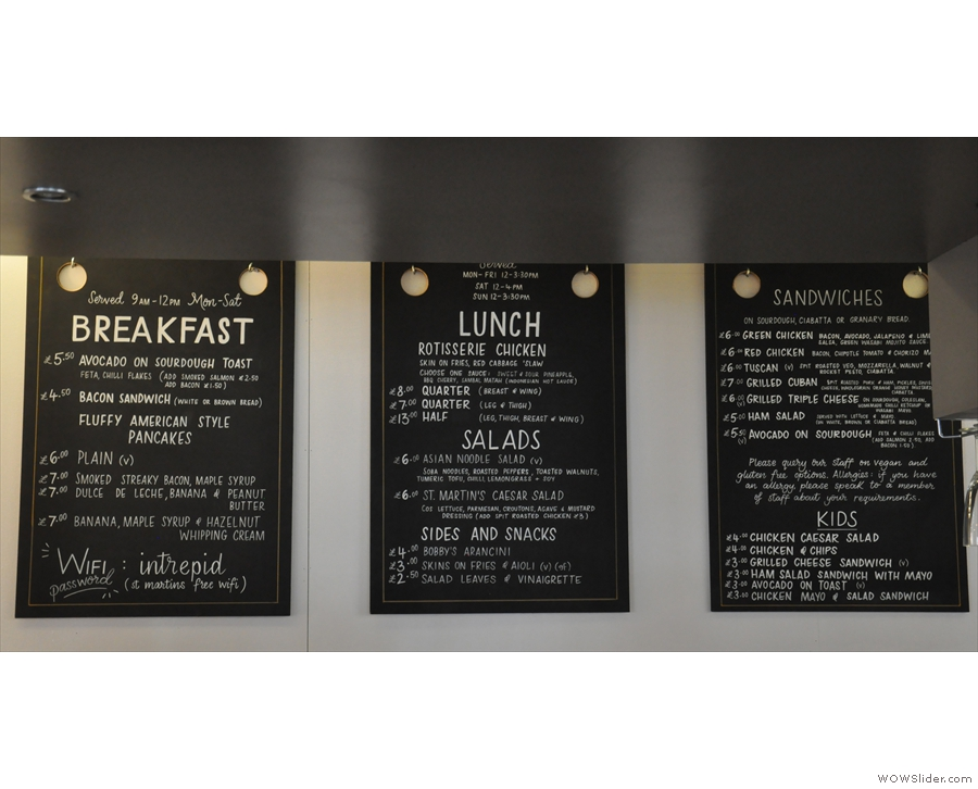 The menus hang on the wall behind and above the counter...