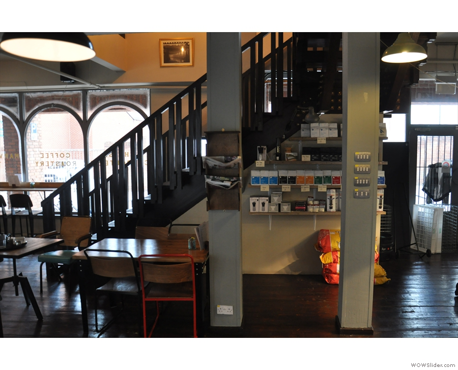 There's a stairway at the back, with some more seating and a set of retail shelves.