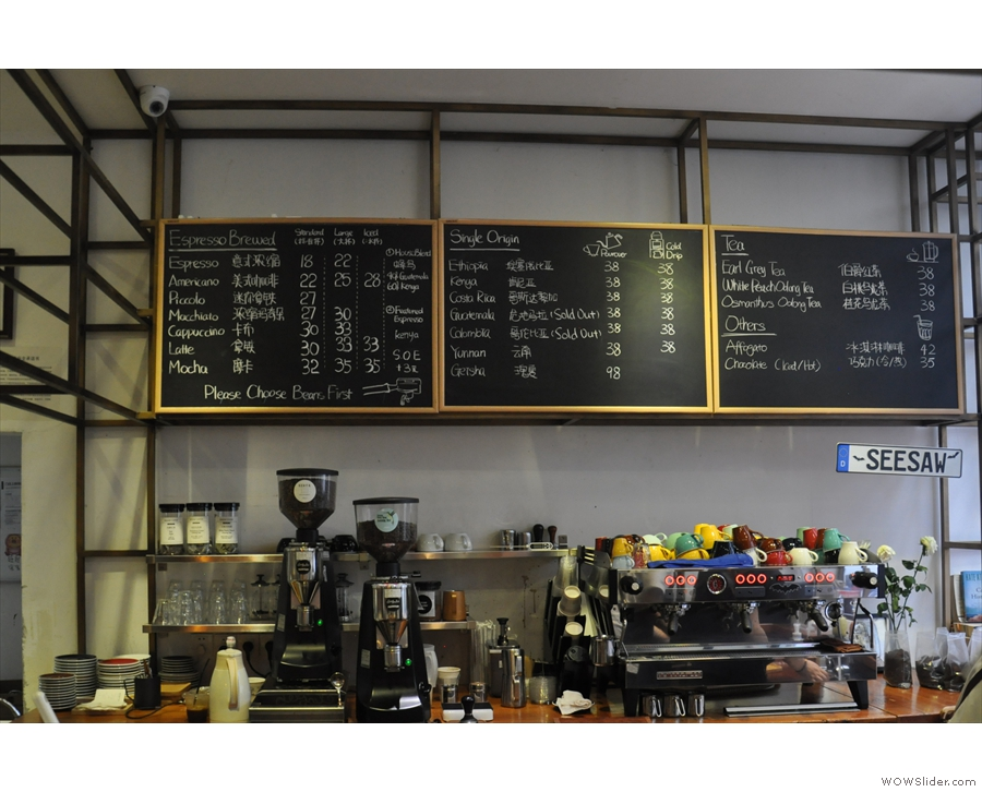 The espresso machine and grinders are on the back wall, menu above.