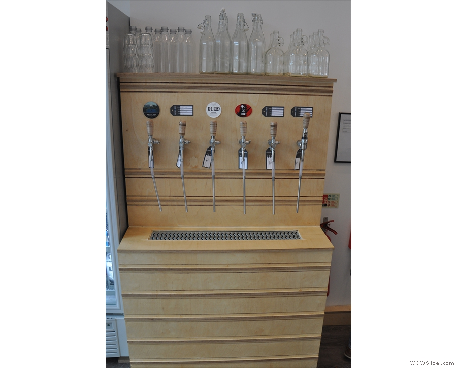 The fridge holds cold beer, but this caught my eye: a line of beer taps, bottles above.