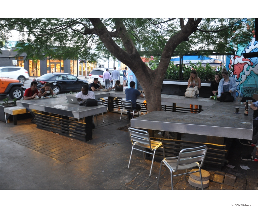 A concrete-topped table forms in a near square, seating provided by benches & chairs.
