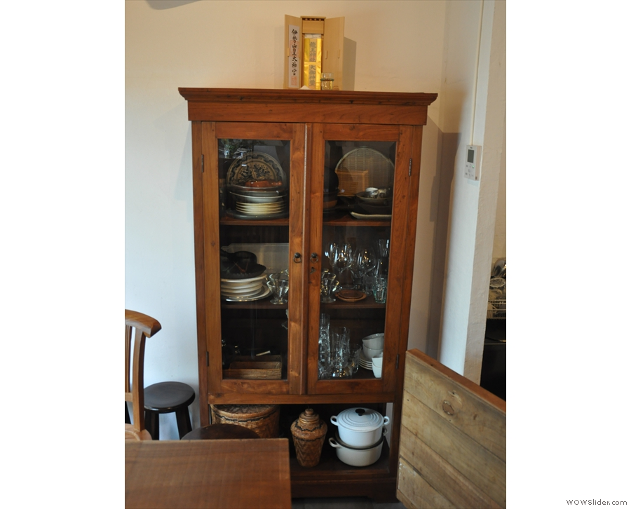 There's a cabinet full of crokery and glassware against the right-hand wall at the back.