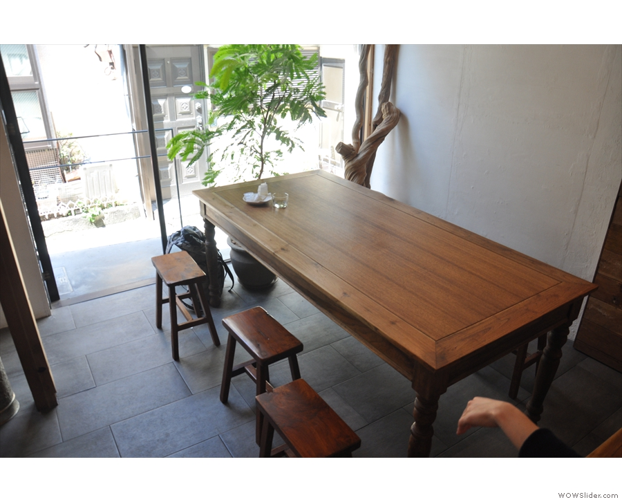 The seating, starting with this large, communal table, is on the left and at the back.