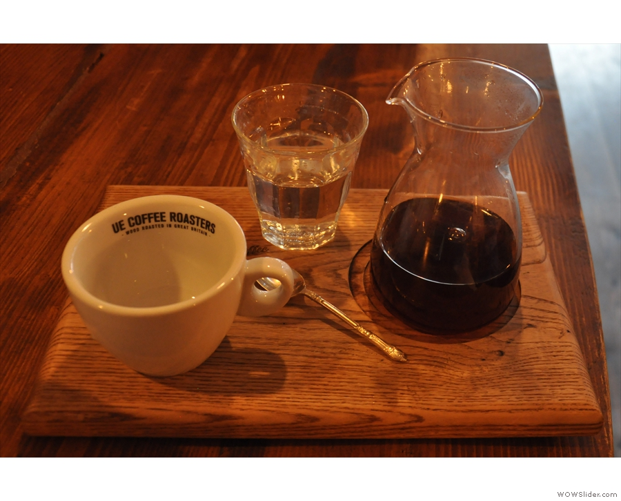 The presentation of the coffee is excellent, served on a wooden tray.