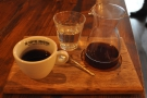 The coffee is poured in a carafe, with a cup on the side and a glass of water.