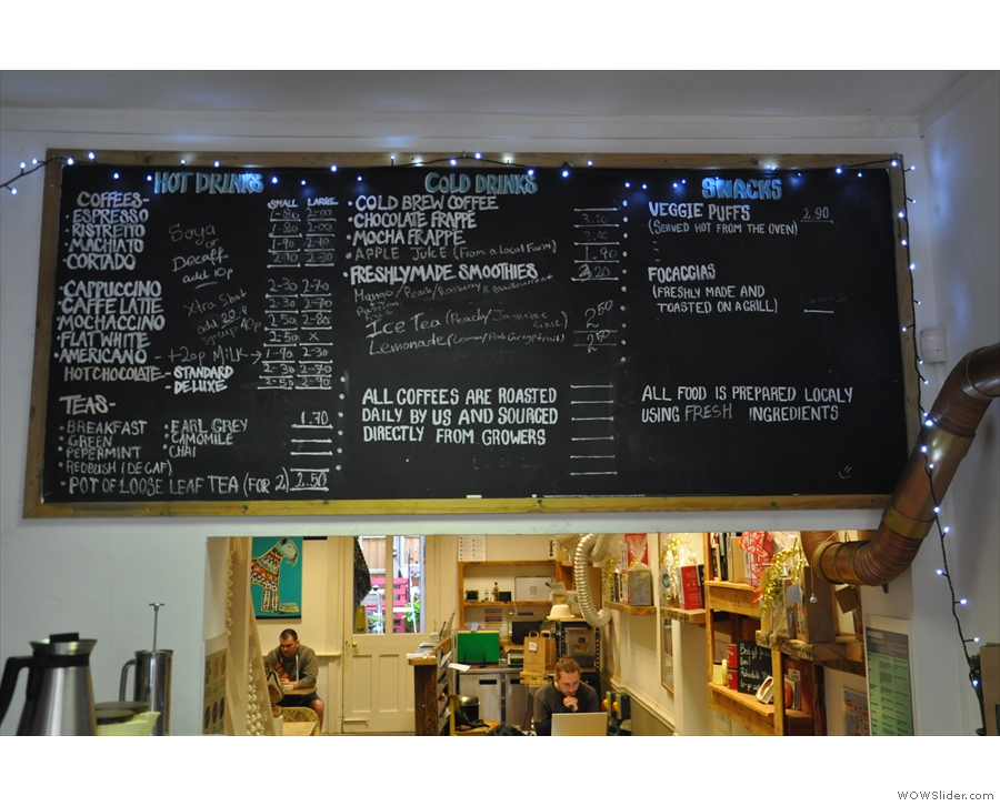 The menu is on the wall at the back of the room to the right of the counter.