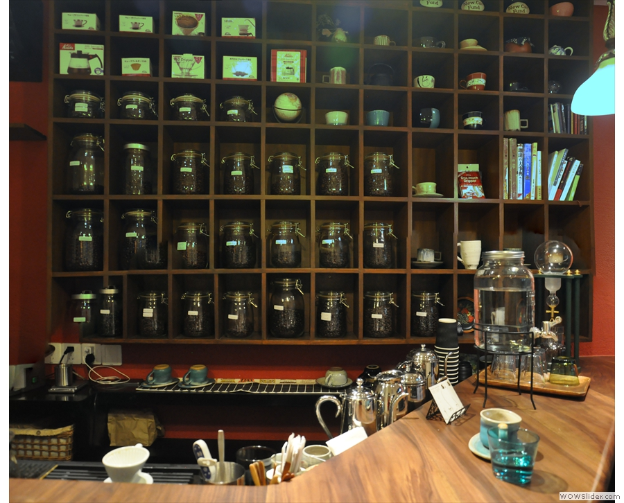 The counter is at the back, with rows of coffee beans in jars behind it.