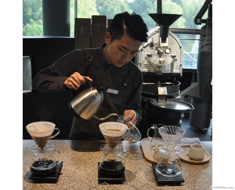 While the two V60s are brewing, the barista prepares the carafes and cups, warming them.