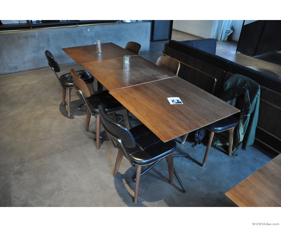 There is a row of two-person tables pushed together to form a set of two & one of three.
