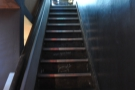 ... leads to a flight of stairs running along the left-hand wall...