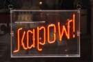 Meanwhile, on the other side, is a neon sign. Where are we again?