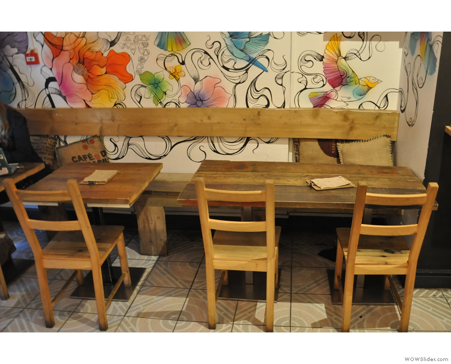 These line a wooden bench along the wall. Check out the menus on the tables.