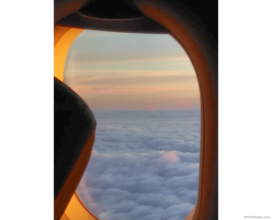 We broke thrrough the clouds shortly after takeoff to be greeted by dawn's warm glow.